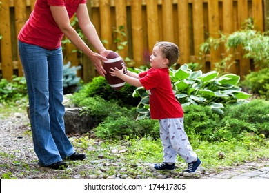 A small boy receives a hand off from his mommy in a game of backyard football.