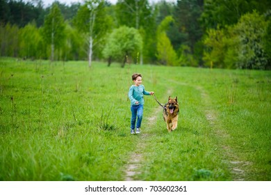 a small boy runs along a overgrown dirt road and holds a huge German shepherd dog for leash