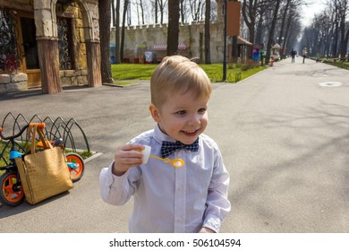 Small boy in shirt is playing with bubbles and laughing