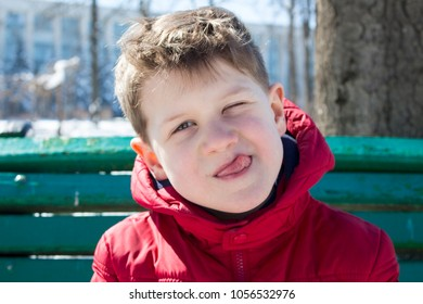Small boy shows his tongue and make face. Funny cheerful child has fun outdoor in sunny day. Concept of childhood.