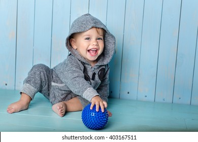 small boy sits, smiles and keeps the ball
