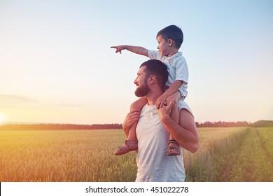 Kleiner Junge sitzt auf seinem Vater? auf den Schultern seines Vaters und zeigt bei schönem Sonnenuntergang auf die Sonne auf dem Feld.