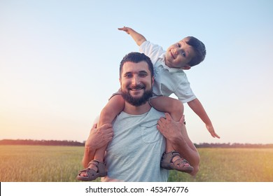 Small boy is sitting on his father's shoulders and pretending a plane during walk in the field