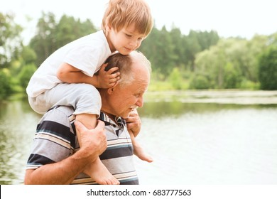 Small boy is sitting on his grandfather On Walk in the summer outdoors. Concept of friendly family.