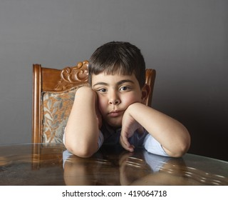 Small boy sitting on wood chair with reflective table in front