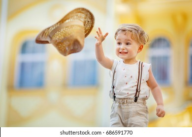 A small boy in a sleeveless shirt and suspenders throws a straw hat aside