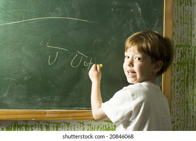 Small boy smiling as he writes on a chalkboard. Horizontally framed photo.