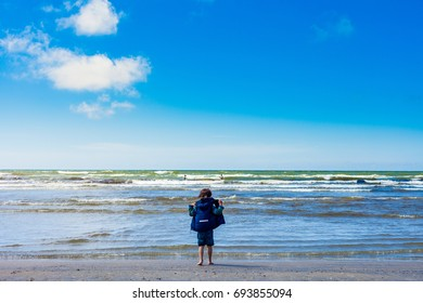 Small boy standing in front of sea and watching waves