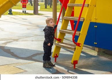 Small boy staying near the ladder
