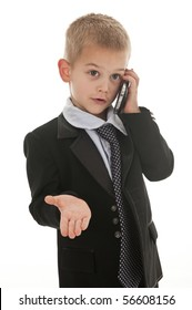 A small boy in the studio, dressed up in a suit and pretending to be a businessman.
