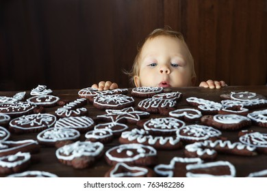 Small boy tries to grab traditional homemade Christmas ginger and chocolate cookie decorated with white sugar painting