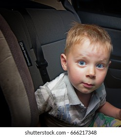 A small boy wearing a seat belt in the car.