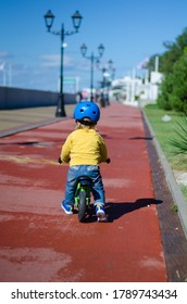 A small boy in a yellow jumper and jeans is walking along the embankment a green running Shoe and a blue helmet and sneakers. Image selective fokus. Focus on the boy.