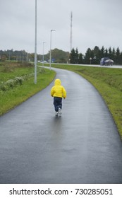 Small boy in yellow running by the wet road. Rainy day.