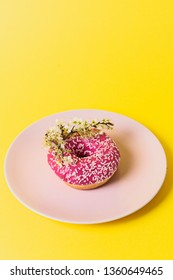 A small branch with tiny white flowers ironically placed over a pink frosted, sugar bomb doughnut sitting on a cute pink plate on a yellow background.