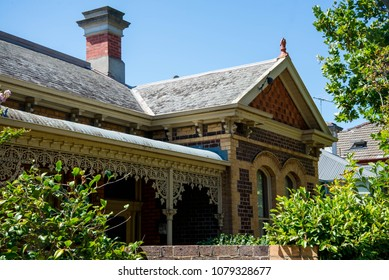 The small brick private house in the Victorian style in a garden with a fence and green trees. Best property in Melbourne. Sweet home in Australia.