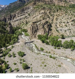 Small bridge crosses a river below massive mountains in the Rockies of Wyoming.