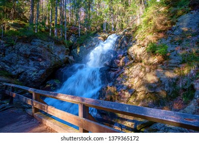 a small bridge in front of a waterfall in the bavarian forest