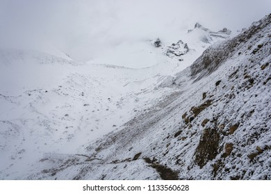 A small bridge on the snow-covered Thorong La pass on a cloudy day, Nepal.