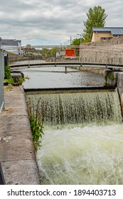 Small bridge over the Eglinton Canal Lock with running water forming small waterfalls, Waterways of Galway, Hydroelectric Engineering, cloudy day in Galway City, Connacht Province, Ireland