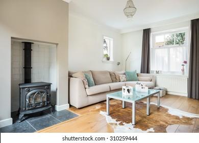 Kleines helles Wohnzimmer mit Sofa und Kamin