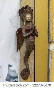 Small bronze sculpture of mermaid godess, made in the shape of door handle and attached to the wall or the yellow door, viewed in close-up.