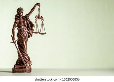 Small bronze statue of Justice with sword and scales wearing a blindfold allegorical of law and order over a pale green background with copy space