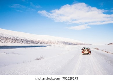 small brown car on roadtrip in iceland in snow ice winter under blue sky