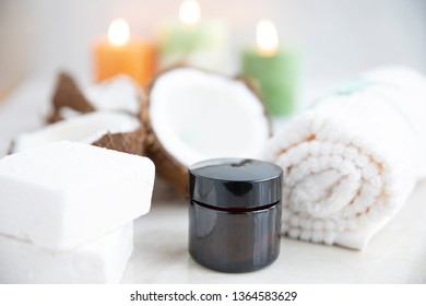 Small brown jar of coconut cosmetic product in spa environment.