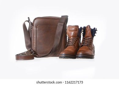 Small brown leather bag with leather shoes on white background