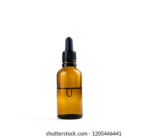 Small brown medical pipette glass bottle isolated on white background. A lot of empty room and space for text.