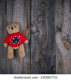 small brown old teddy bear, gray old wooden background, top view