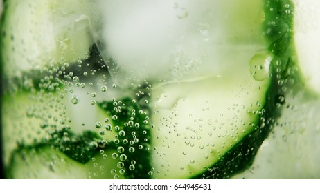 Small bubbles from soda and a drop of water on the wall of a glass with cucumber slices and ice. close-up