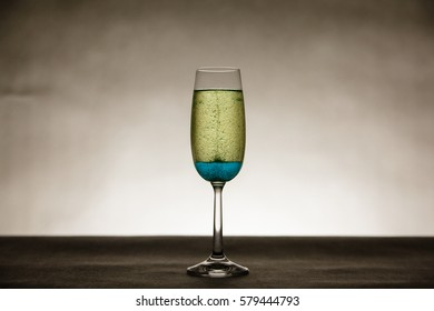 Small bubbles in tall champagne glass