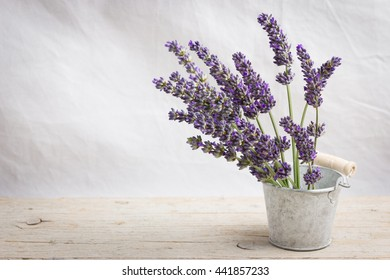 Small bucket with dried  lavender flowers on light background. Space for text
