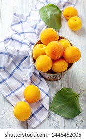 Small bucket with ripe apricots and linen fabric on an old wooden table, selective focus. Top view.