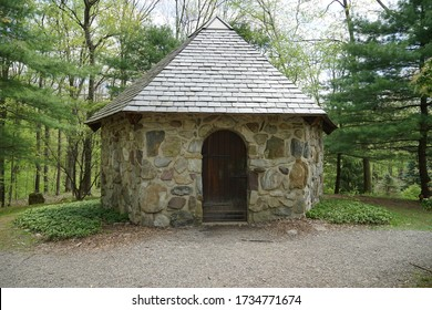 A small building made of rocks in a wooded area.  The structure has a rounded arch wood door and a slate roof.