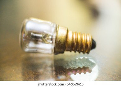 A small bulb lamp. Bulb emits light when screwed onto a lamp that gives it power. There are various sized bulbs. This is clear and bright yellow.