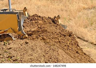 Small bulldozer moves dirt and brush at a new commercial construction development project