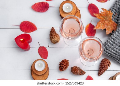 Small burning candles, two glasses with rose wine, cones, dry red leaves, a gray scarf knitted on a white wooden table. Hello, Autumn. Cozy autumn background.