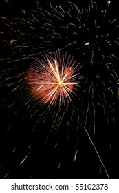 Small burst of fireworks with reddish smoke and thin rocket trail by large cloud of falling embers