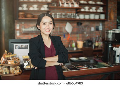Small business, cafe female owner standing behind the counter. Young female barista standing behind the bar in cafe .
