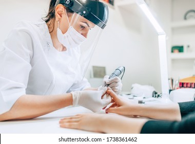 Small business existence at COVID-19 lockdown concept. Professional manicure master in Transparent Safety Face Shield using Electric Nail Polisher Tool for Glazing treatment manicure procedure.