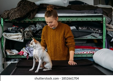 Small business, Fashion designer workplace, Tailoring Shop. Fashion Designer with pet dog Working In Her Studio. Beautiful female designer working in atelier with fabrics.