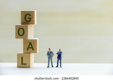 Small business goal setting concept : Miniature CEO and CMO talk on a company goals topic, depicts best / better ways to approach goal setting for a business or entrepreneur / tips for startup goals