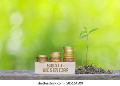 SMALL BUSINESS Golden coin stacked with wooden bar on shallow DOF green background