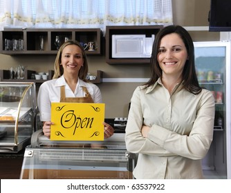 Small business: Happy owner of a cafe showing open sign