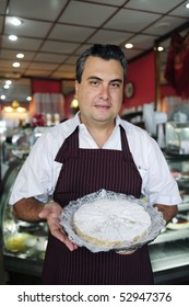 small business: happy waiter showing a tasty cake