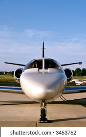 A small business jet waits on the tarmac for its passengers