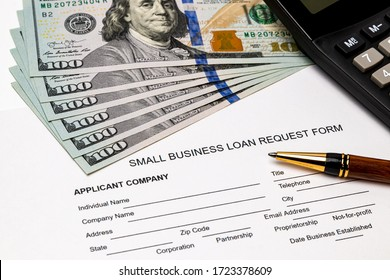 Small business loan form, 100 dollar bills. Concept of financial assistance, stimulus payment and recession during Covid-19 coronavirus pandemic